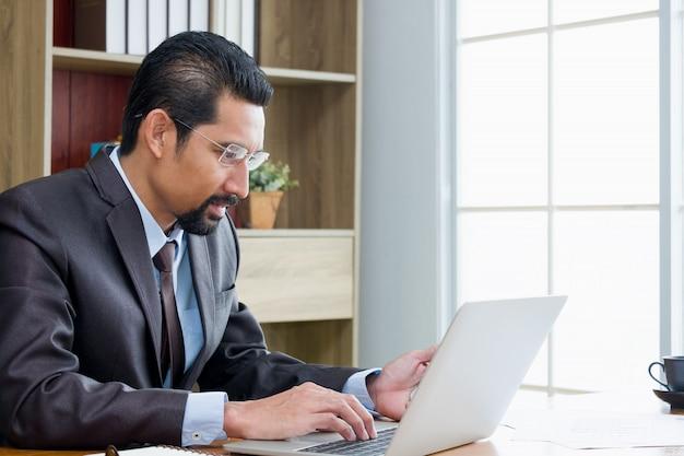 Empresário adulto usando um laptop no local de trabalho.