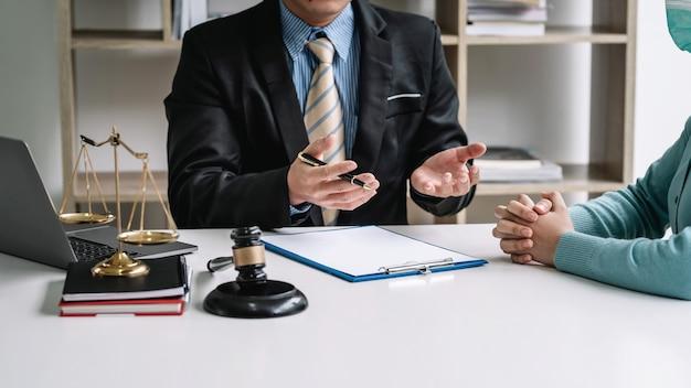 Empresário advogado com clientes faz um contrato para trabalhar o martelo colocado na mesa do escritório.