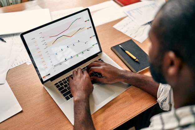 Empresário africano analisando estatísticas na tela do laptop, trabalhando com gráficos financeiros na internet, usando software empresarial para análise de dados e conceito de gerenciamento de projeto, vista traseira em close-up