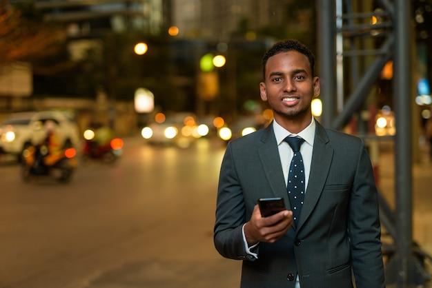 Empresário africano ao ar livre à noite segurando o telefone ao lado da rua enquanto sorri