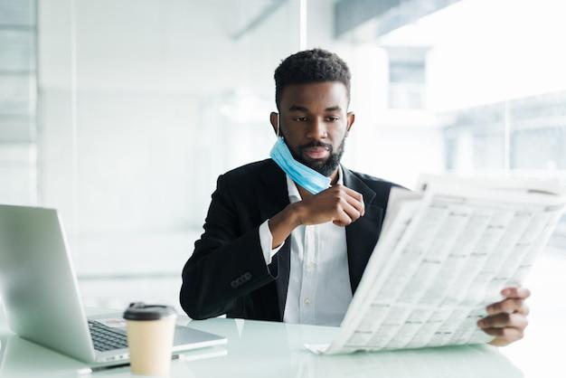 Empresário africano bonito usar máscara médica com jornal da manhã perto do escritório do centro de negócios