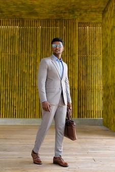 Empresário africano caminhando ao ar livre e parecendo elegante e descolado, tiro completo