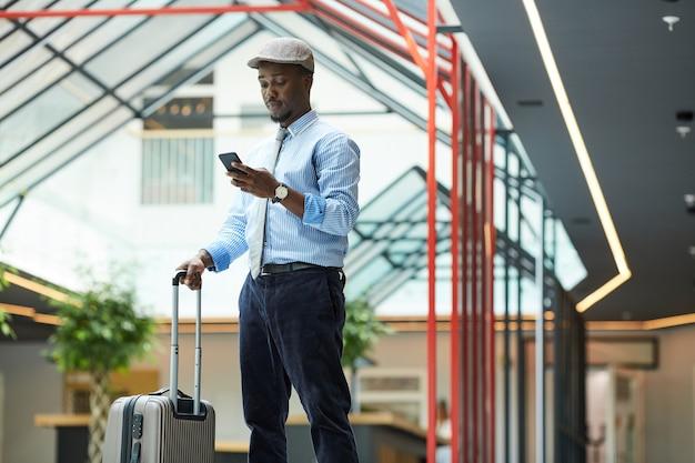 Empresário africano com mala de pé no aeroporto e usando seu telefone celular