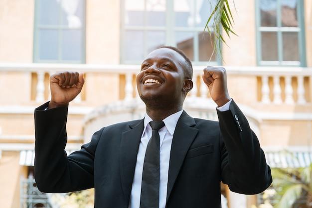 Empresário africano com mãos ao alto comemorando sucesso
