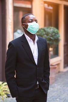 Empresário africano com máscara médica para proteger do vírus da coroa ou covid-19