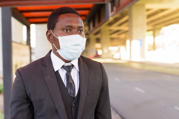 Empresário africano com máscara pensando enquanto espera no ponto de ônibus