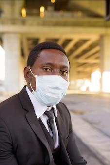 Empresário africano com máscara sentado no ponto de ônibus na cidade