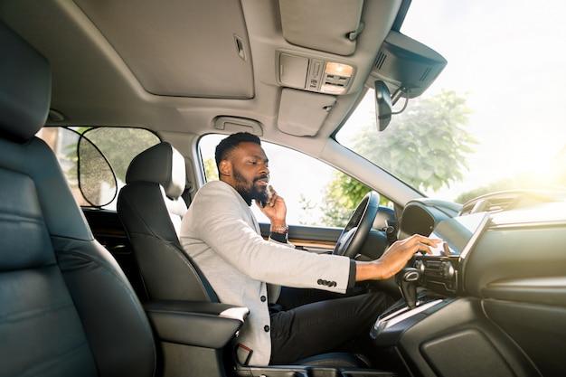 Empresário africano falando no celular dentro de um carro e tocando o tablet. jovem empreendedor trabalhando durante a viagem ao escritório em um carro de luxo.