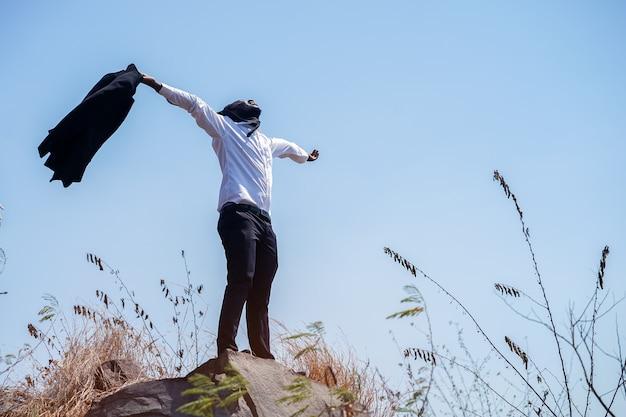 Empresário africano liberdade tirar o fato e de pé no topo da montanha