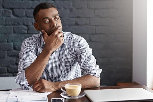 Empresário africano pensativo tocando seu queixo