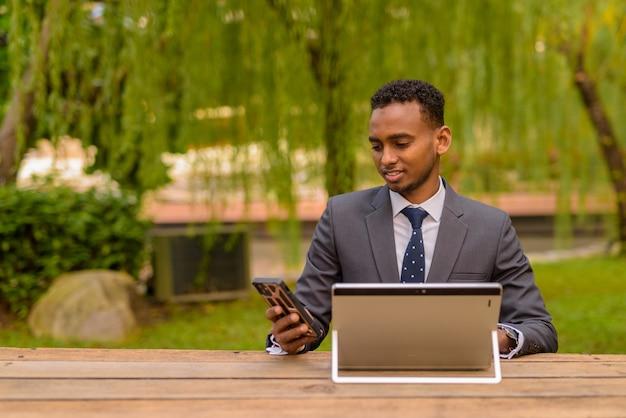 Empresário africano sentado ao ar livre usando um laptop e um telefone