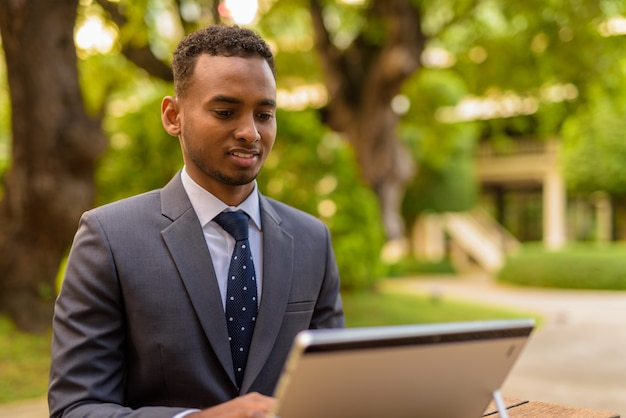 Empresário africano sentado ao ar livre usando um laptop enquanto sorri