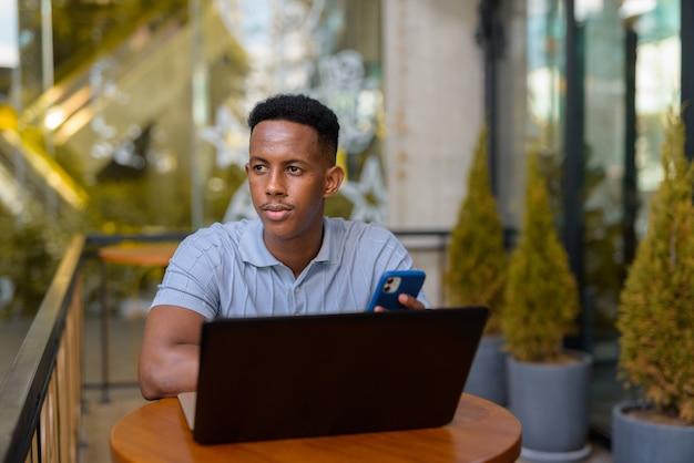 Empresário africano sentado em uma cafeteria enquanto usa um laptop e telefone celular enquanto pensa