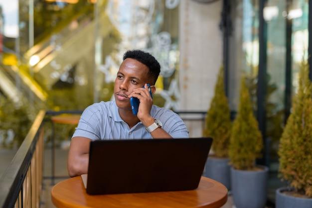 Empresário africano sentado em uma cafeteria, usando um laptop e falando no celular