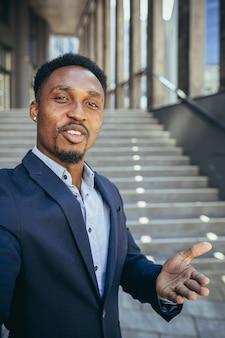 Empresário africano usa videochamada olhando para a câmera e se comunicando com colegas