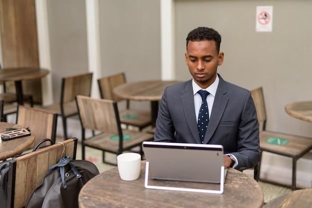 Empresário africano usando laptop enquanto se distancia socialmente em uma cafeteria