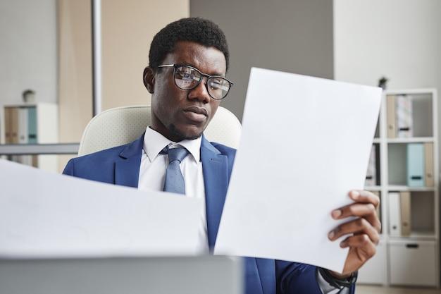 Empresário africano usando óculos e segurando papéis nas mãos, examinando documentos enquanto trabalhava no escritório