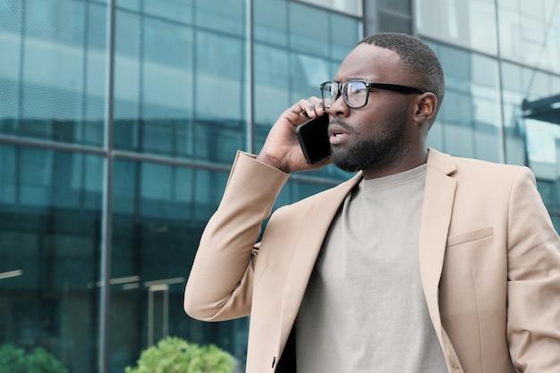 Empresário africano usando óculos falando no celular enquanto caminha pela rua da cidade