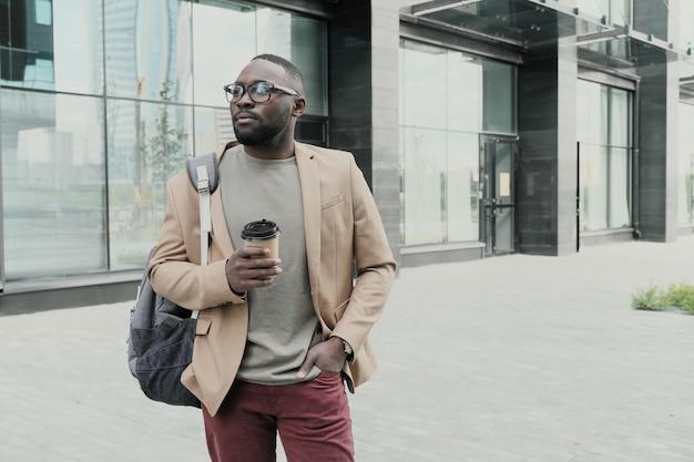 Empresário africano usando óculos tomando café durante o intervalo para o café na cidade