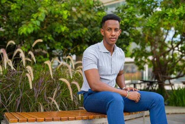 Empresário africano vestindo roupas casuais e sentado no banco do parque enquanto olha para a frente