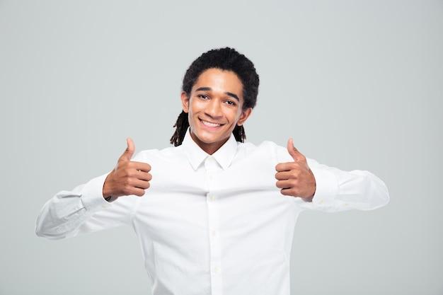 Empresário afro-americano alegre mostrando os polegares para cima sobre uma parede cinza
