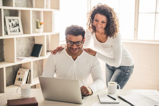Empresário afro-americano bonito está usando um laptop