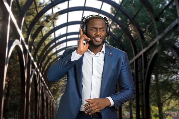 Empresário afro-americano com fones de ouvido ao ar livre. homem negro com roupa formal ouvindo música e curtindo o ritmo