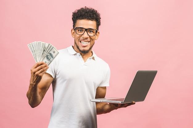 Empresário afro-americano de sucesso segurando dinheiro em uma mão e laptop na outra