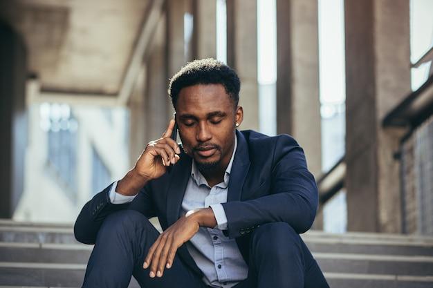 Empresário afro-americano deprimido, contando notícias tristes, falando ao celular, sentado na escada do escritório, em um terno de negócio