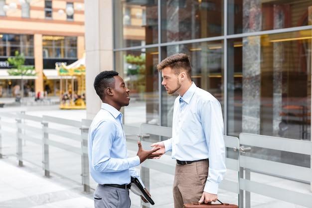 Empresário afro-americano e um empresário caucasiano discutindo e examinando os documentos na cidade