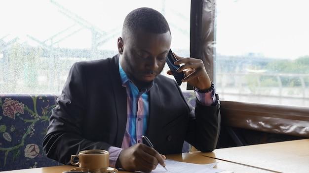 Empresário afro-americano está ligando para smartphone e bebendo café no café.