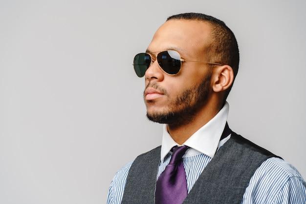 Empresário afro-americano, usando óculos retrato sobre cinza.