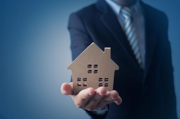 Empresário, agência banqueiro segurando modelo de casa e apresentar imóveis