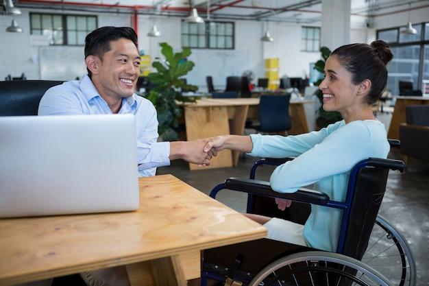 Empresário, agitando as mãos com colega com deficiência