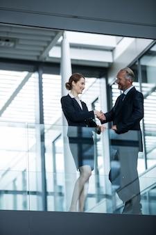Empresário, agitando as mãos com colega