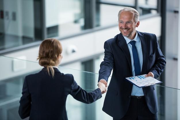 Empresário, agitando as mãos com seu colega