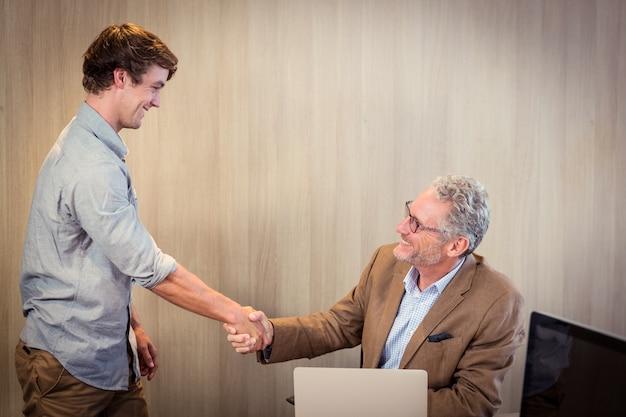 Empresário, agitando as mãos com um colega de trabalho