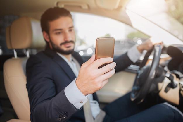 Empresário agradável e alegre senta-se em carro de luxo. ele segura o telefone em uma mão e olha para a tela. outra mão está no volante.