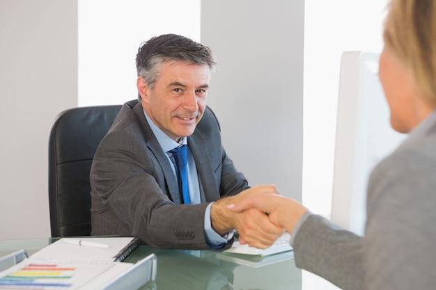 Empresário alegre, apertando a mão de um entrevistado