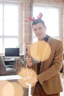 Empresário alegre com tiara de natal olhando para você enquanto está ao lado da máquina de xerox e tomando chá ou café no intervalo no ambiente de escritório