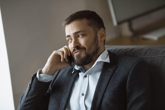 Empresário alegre de terno falando ao telefone, sentado no sofá no escritório.