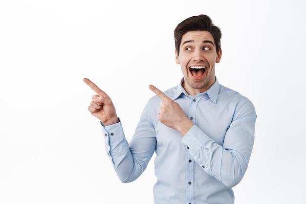 Empresário alegre ofegando fascinado, olhando e apontando para o lado esquerdo, mostrando um anúncio, em pé sobre uma parede branca em uma camisa de colarinho azul