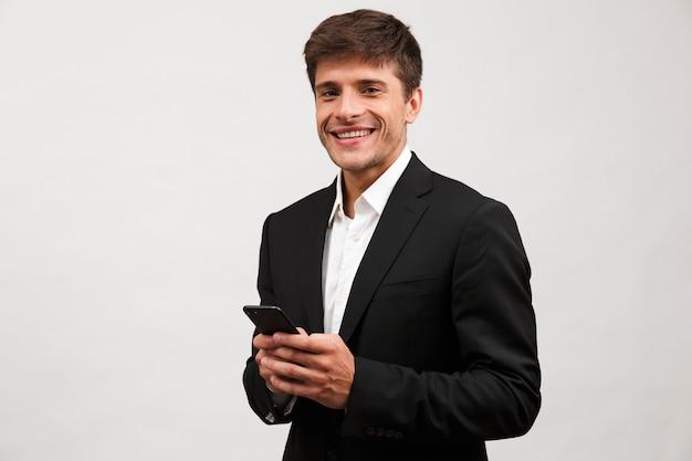 Empresário alegre parado, isolado, conversando ao celular