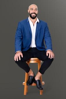 Empresário alegre sentado em um banquinho de madeira, empregos e campanha profissional