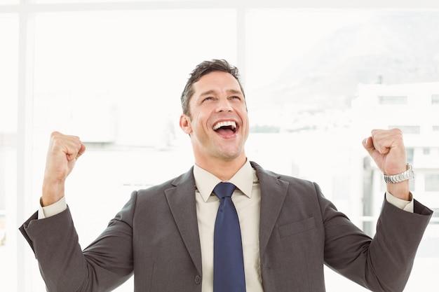 Empresário alegre torcendo no escritório
