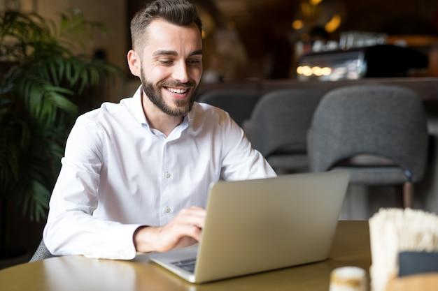 Empresário alegre trabalhando no café