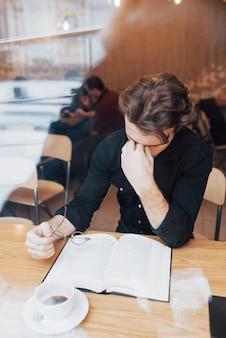 Empresário alegre vestido de camisa branca sentado em um café e lendo um livro