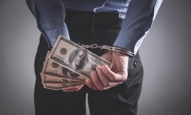 Empresário algemado, segurando notas de dólar. corrupção