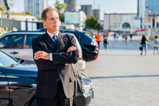 Empresário amadurecido com braços cruzados em pé na rua