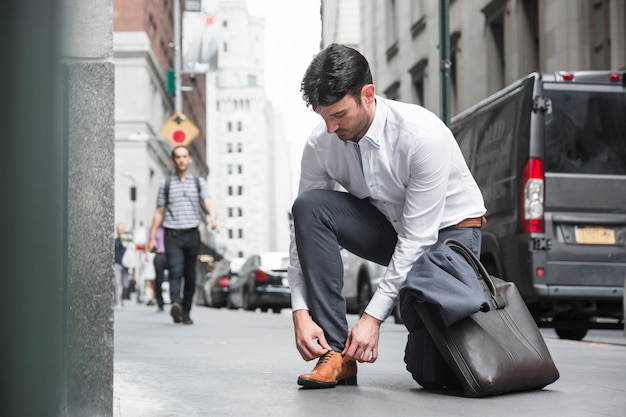 Empresário amarrar cadarços perto da estrada